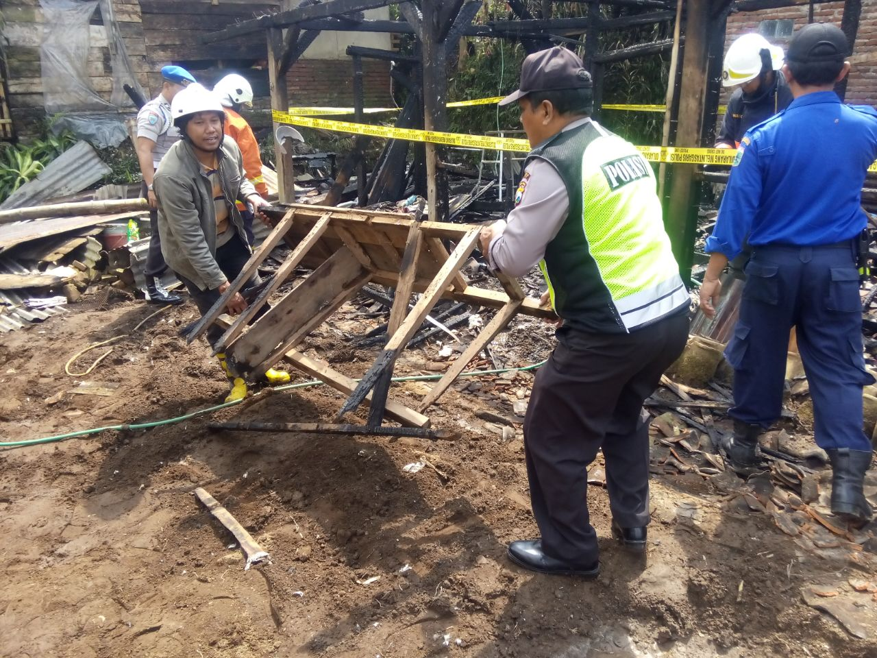 Anggota Polsek Bumiaji membantu korban kebakaran rumah di Ds. Tulungrejo