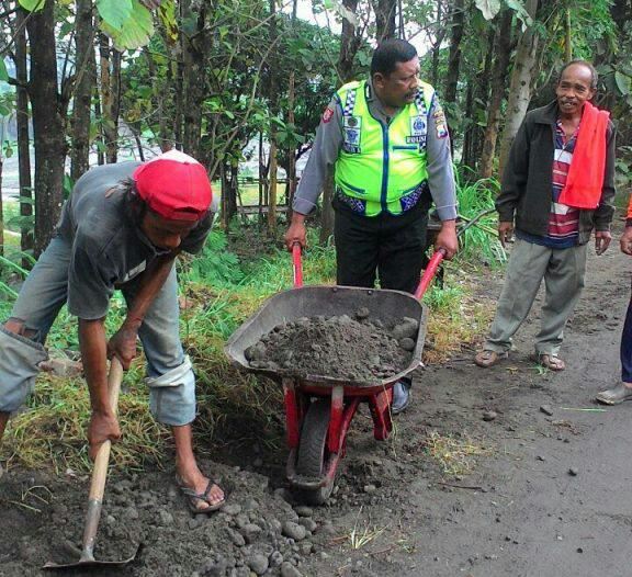 Kanit Binmas Polsek Kasembon Polres Batu Membantu Warga Memperbaiki Jalan