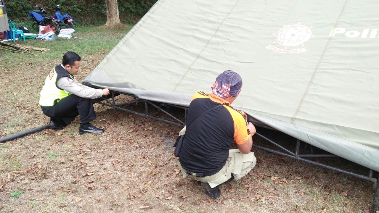 Anggota Polsek Ngantang Polres Batu membantu mendirikan Tenda persiapan Jambore Pol PP se Wilayah Polsek Ngantang ke XV di Taman wisata Selorejo
