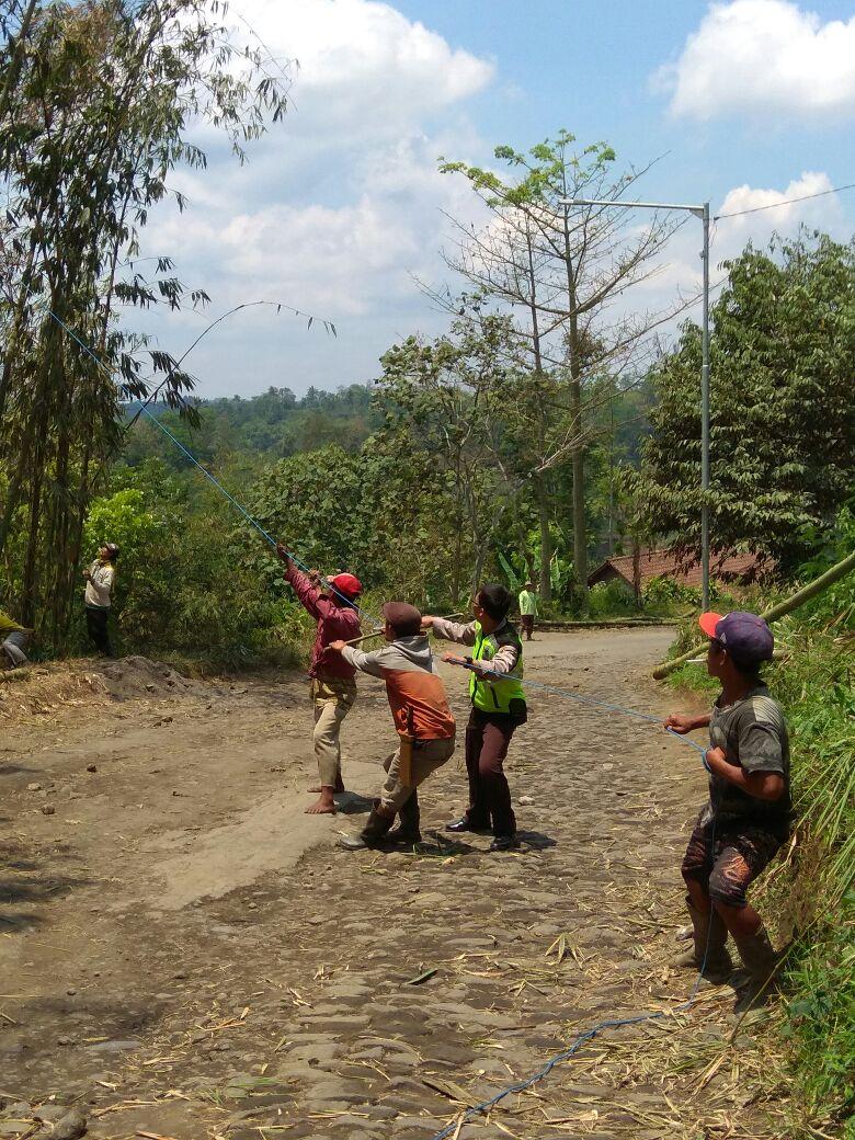 Bhabinkamtibmas Desa Pagersari Polres Batu Bersama Warga Membersihkan Bambu Tumbang di Tengah Jalan