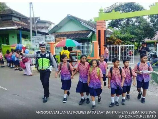 Polisi Lalu Lintas Polres Batu Menyeberangkan Anak SD di Pagi Hari