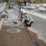 Bhabinkamtibmas Desa Kaumrejo Polsek Ngantang Polres Batu Membantu Warga Memperbaiki Jalan Berlubang