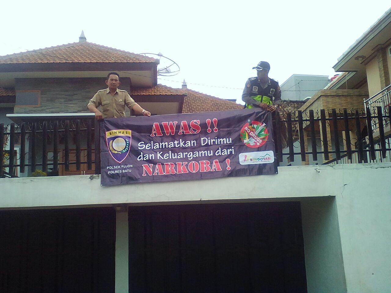 Bhabinkamtibmas Polsek Pujon Polres Batu Memasang Banner Bahaya Narkoba di Balai Desa Bendosari