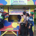 Anggota Bhabinkamtibmas Kel. Songgokerto menempelkan banner himbauan kamtibmas dengan dibantu oleh komunitas ojek
