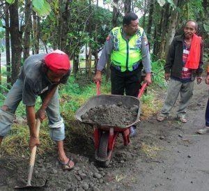Anggota Bhabinkamtibmas Polsek Kasembon Polres Batu Bantu Warga Memperbaiki Jalan Yang Rusak