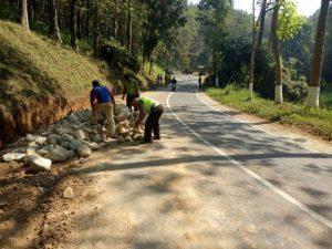Anggota Polsek Kasembon Polres Batu Bantu Warga Tepikan Material Batu Di Jalan