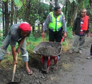 Anggota Bhabinkamtibmas Polsek Kasembon Polres Batu Membantu Warga Desa Binaan Memperbaiki Jalan
