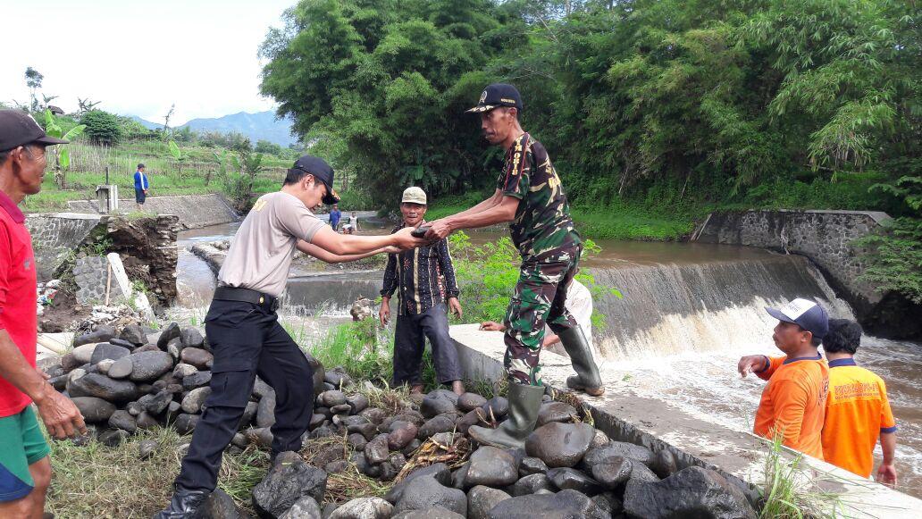 Anggota Polres Batu – Sektor Junrejo Karya Bhakti membantu warga terkena bencana alam