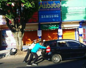 Anggota Satlantas Polres Batu Membantu Mendorong Mobil Yang Mogok