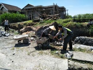 Anggota Bhabinkamtibmas Polsek Pujon Polres Batu Giat Kerja Bakti Bersama Warga Desa Binaan