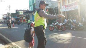 Anggota Polsek Bumiaji Polres Batu Awali Yanmas Dengan Pos Awal Menyebrangkan Anak Sekolah