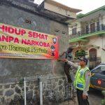 Anggota Binmas Polsek Pujon Polres Batu memasang Banner Bahaya Penyalahgunaan Narkoba