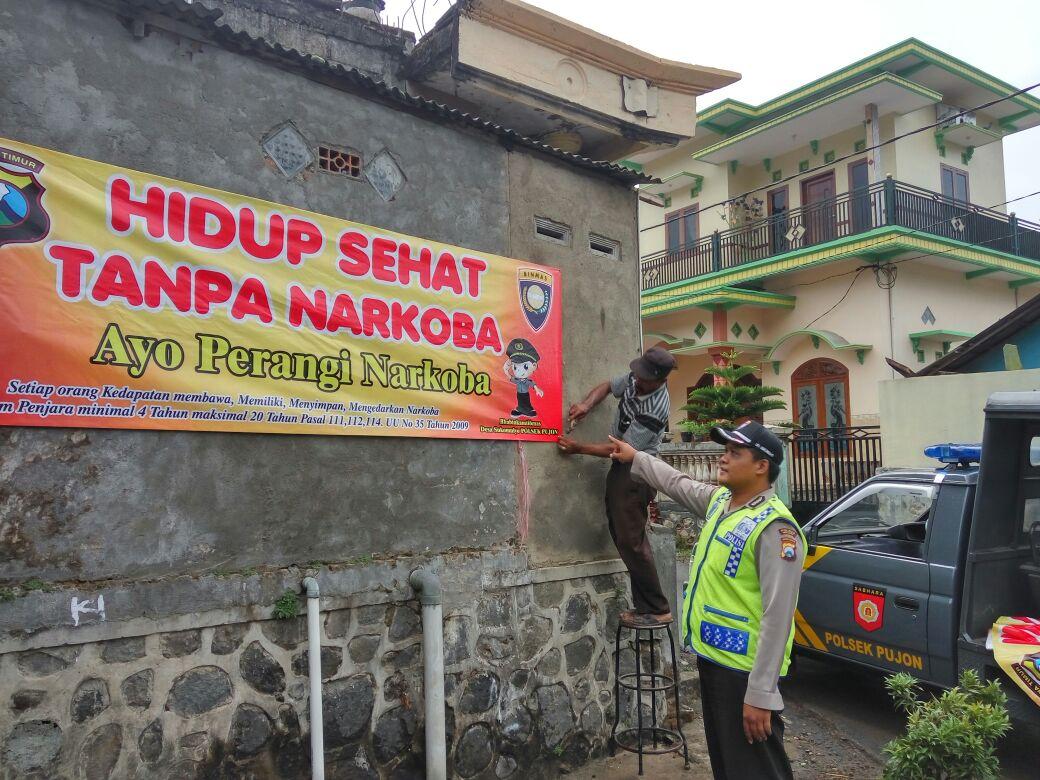 Binmas Polsek Pujon Polres Batu, Melaksanakan Pemasangan Banner Bahaya Penyalahgunaan Narkoba di Masyarakat