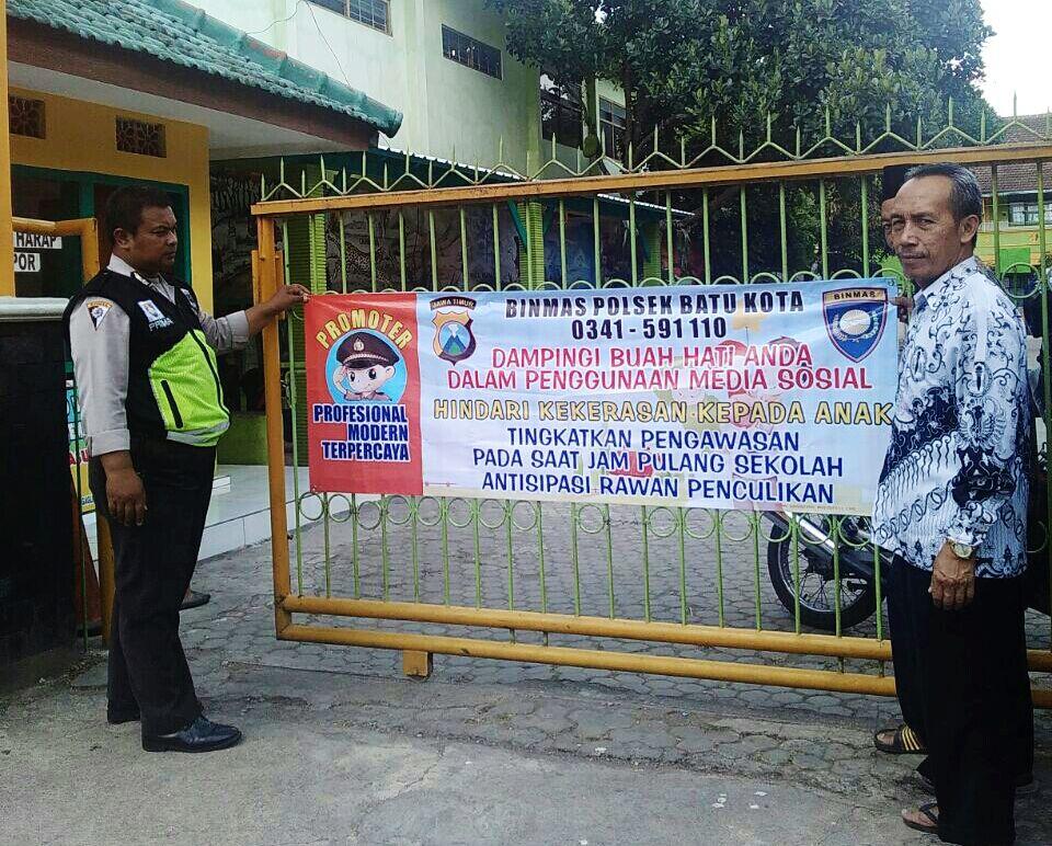 Cegah Kekerasan Anak, Kanit Binmas Polsek Batu Polres Batu Giatkan Pemasangan Banner Di pagar Halaman Sekolah