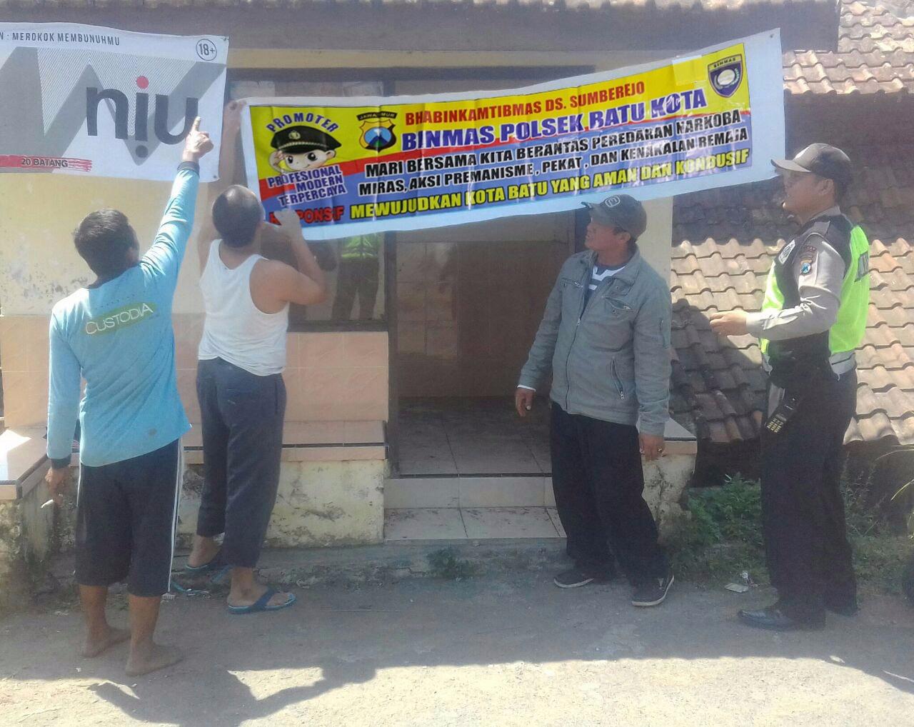 Berantas Narkoba, Bhabin Polsek Batu Kota Polres Batu Giat Pemasangan Banner Himbauan Kamtibmas Di Pos Pos Kewilayahan
