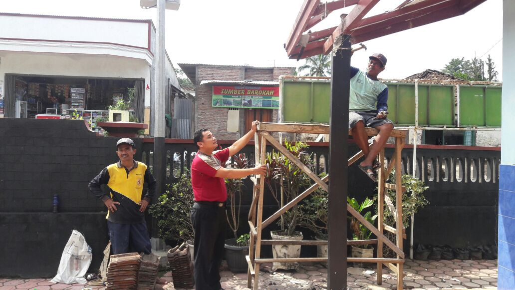 Bhabin Polsek Ngantang Polres Batu Kawal ADD Lakukan Rehab Teras Kantor Desa Purworejo