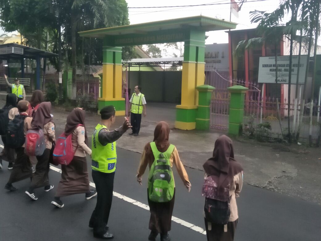 Polsek Ngantang Polres Batu Lakukan Pelayanan Poros Pagi Menyebrangkan Siswa Sekolah