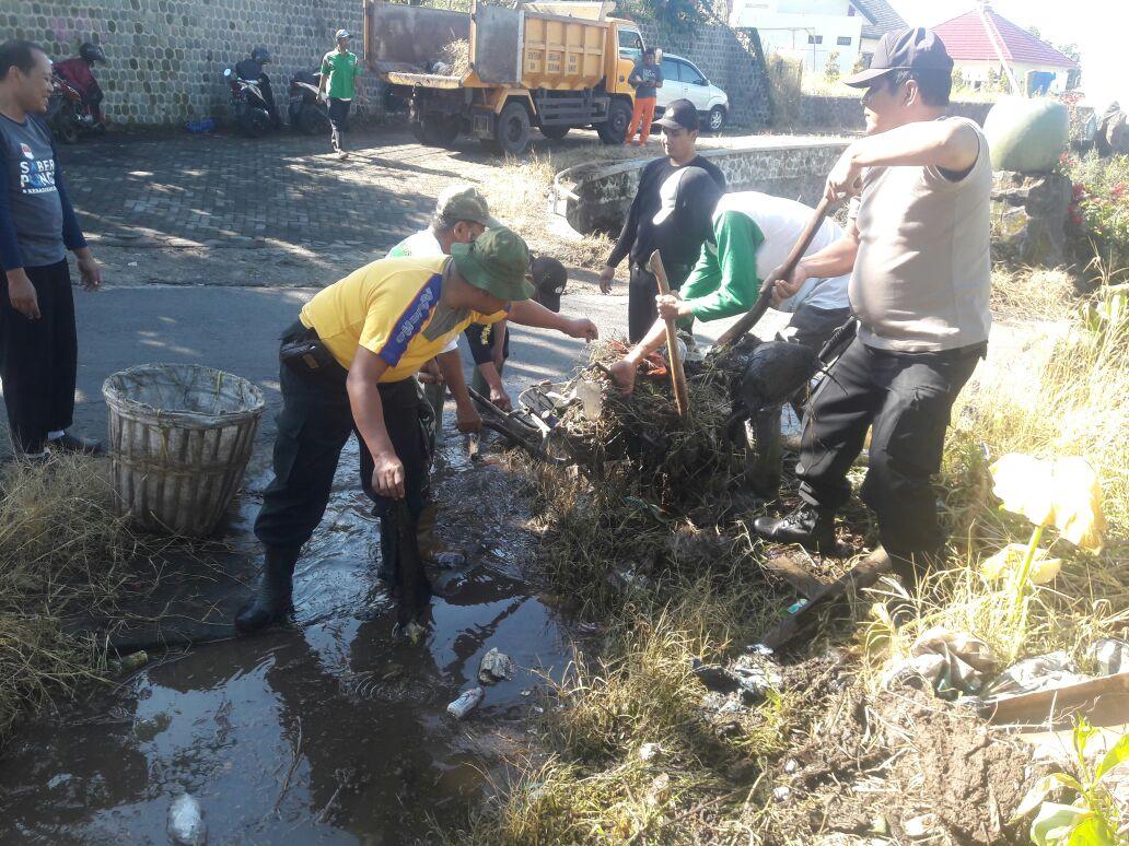 Kapolsek Bumiaji Polres Batu  Melaksanakan Kerja Bakti Bantu Masyarakat Untuk Membersihkan Desa