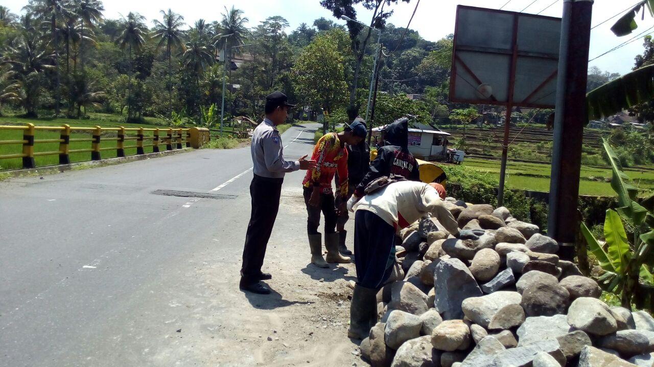 Anggota Bhabinkamtibmas polsek Kasembon Polres batu Giat Patroli Dan Membantu Warga Yang Sedang Bekerja Memasang Bronjong Jembatan