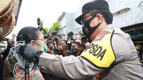 Kapolda Jatim Memakaikan Masker Secara Langsung ke Masyarakat Saat Pembagian Masker di Pasar Simo